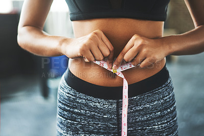 Buy stock photo Cropped shot of a fit young woman measuring her waist in a gym