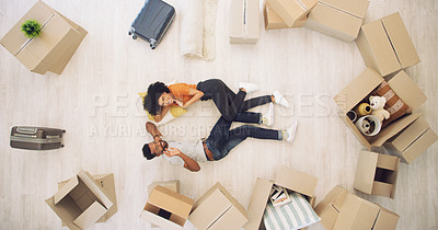 Buy stock photo High angle shot of a young couple lying on the floor and waving while moving house