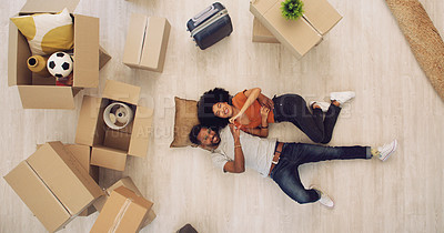 Buy stock photo High angle shot of a young couple lying on the floor and making a heart shape with their hands while moving house