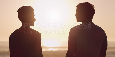 Buy stock photo Cropped shot of an affectionate young couple smiling at each other while standing at the beach at sunset