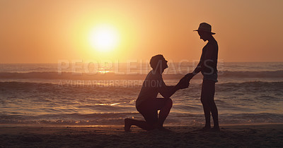 Buy stock photo Full length shot of an affectionate young man proposing to his girlfriend on the beach at sunset