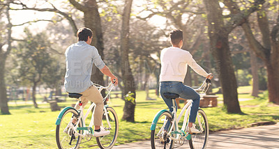 Buy stock photo Rearview shot of an unrecognizable couple cycling together outdoors