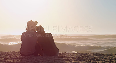 Buy stock photo Rearview shot of an unrecognizable couple sitting together on the beach sand at sunset