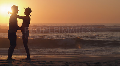 Buy stock photo Full length shot of an affectionate young couple embracing each other while standing at the beach at sunset