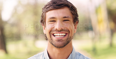 Buy stock photo Cropped portrait of a handsome young man smiling while standing in a park