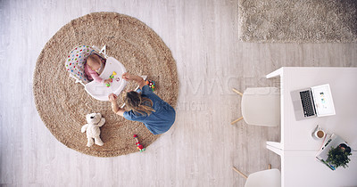 Buy stock photo High angle shot of a mother playing with her baby daughter in a high chair at home