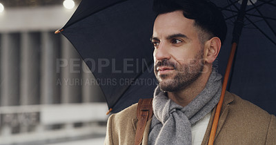 Buy stock photo Cropped shot of a handsome young businessman looking contemplative while standing in the city alone and holding an umbrella