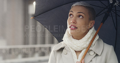 Buy stock photo Cropped shot of an attractive young businesswoman looking contemplative while standing in the city alone and holding an umbrella
