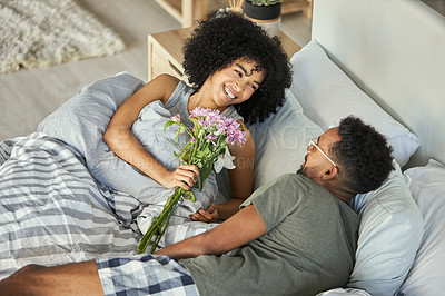 Buy stock photo Shot of a romantic young man giving his partner flowers in their bedroom