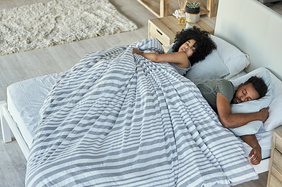 Buy stock photo Shot of a woman getting irritate with her boyfriend who has most of the duvet while lying in bed