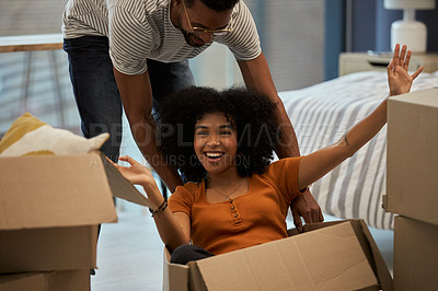 Buy stock photo Shot of a young playful couple moving into their new house
