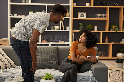 Buy stock photo Shot of a young couple having an argument in their living room