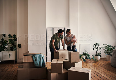 Buy stock photo Full length shot of an affectionate young couple smiling at their baby while standing in their new home on moving day