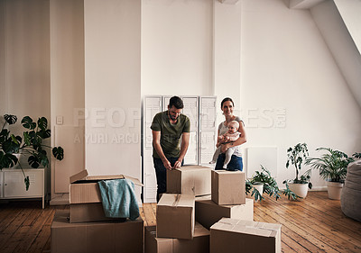 Buy stock photo Full length shot of an affectionate young father opening a box while his wife is carry their baby in their new home on moving day