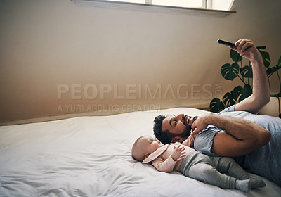 Buy stock photo Cropped shot of an affectionate young father taking selfies with his little baby girl while lying on a bed at home