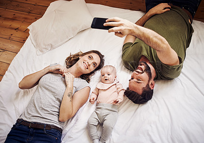 Buy stock photo High angle shot of an affectionate young couple taking a selfie with their little baby girl while lying on a bed at home