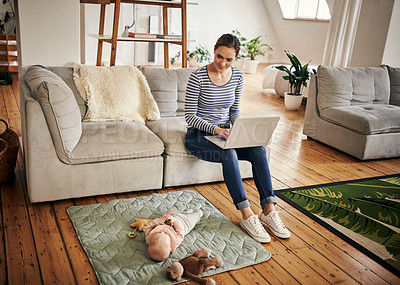 Buy stock photo Full length shot of an affectionate young mother looking at her little baby girl while using a laptop in their living room at home