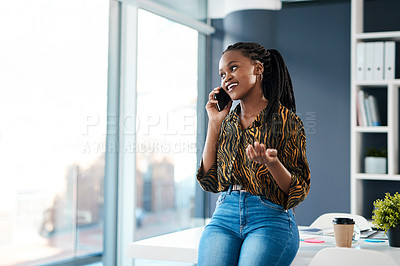 Buy stock photo Cropped shot of an attractive young businesswoman sitting in her office and talking on her cellphone