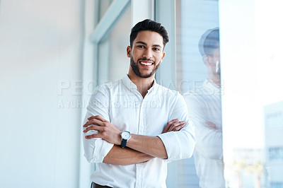 Buy stock photo Cropped portrait of a handsome young businessman standing with his arms folded in his office alone