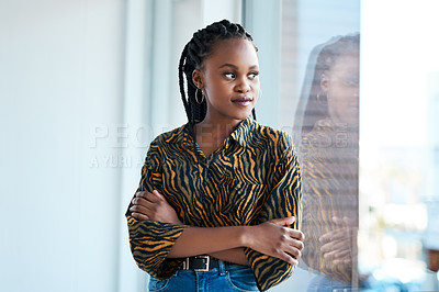 Buy stock photo Cropped shot of an attractive young businesswoman looking contemplative while standing with her arms folded in her office alone