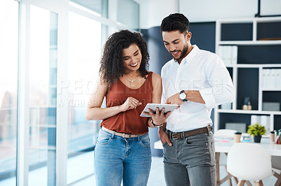 Buy stock photo Cropped shot of two young business colleagues standing together in the office and using a tablet