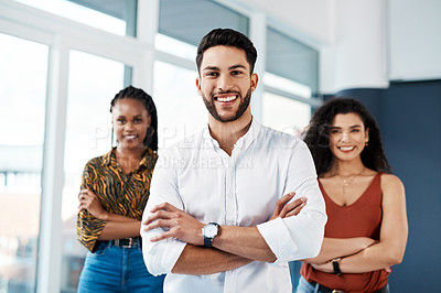 Buy stock photo Cropped portrait of a handsome young businessman standing with his arms crossed in front of his colleagues in the office