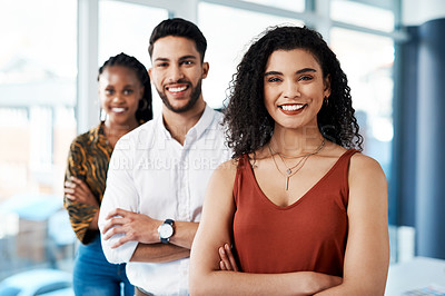 Buy stock photo Cropped portrait of an attractive young businesswoman standing with her arms crossed in front of her colleagues in the office