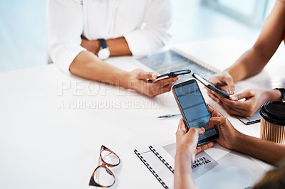 Buy stock photo Cropped shot of an unrecognizable group of businesspeople sitting in the office together and texting on their cellphones