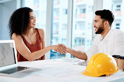 Buy stock photo Cropped shot of two young businesspeople sitting together and shaking hands in agreement with building renovation plans