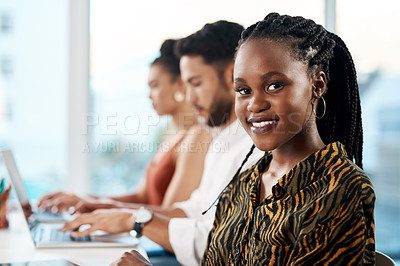 Buy stock photo Cropped portrait of an attractive young businesswoman sitting in the office while her colleagues work on laptops behind her