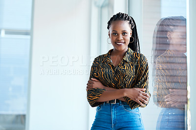 Buy stock photo Cropped portrait of an attractive young businesswoman standing with her arms folded in her office alone