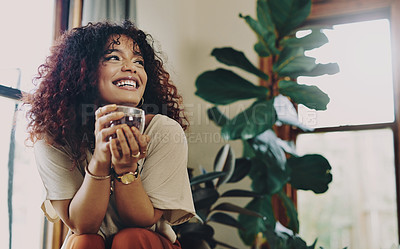 Buy stock photo Cropped shot of an attractive young woman drinking tea while relaxing at home