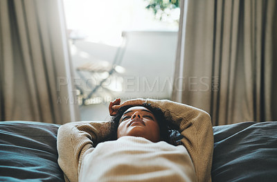 Buy stock photo Cropped shot of a young woman lying on her bed with her eyes closed