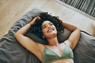 Buy stock photo Shot of a beautiful young woman wearing underwear while relaxing in her bedroom