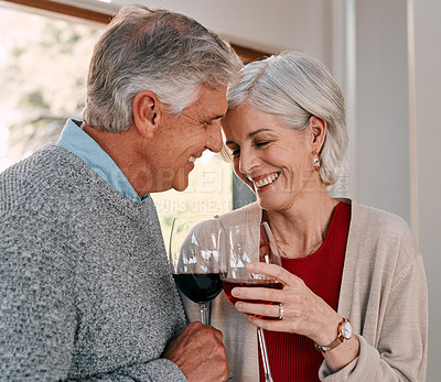Buy stock photo Shot of a happy mature couple having red wine together during a relaxing day at home