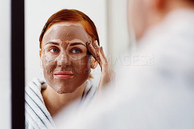 Buy stock photo Cropped shot of an attractive young woman applying a mud mask on her face while standing in front of the mirror in her bathroom at home