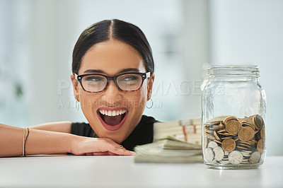 Buy stock photo Cropped shot of an attractive young businesswoman looking excitedly over at a jar of coins and wads of cash in her office