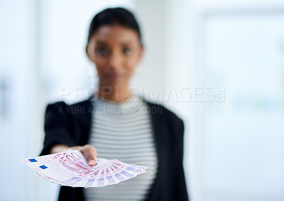 Buy stock photo Defocused shot of a young businesswoman holding a stack of money inside her office at work
