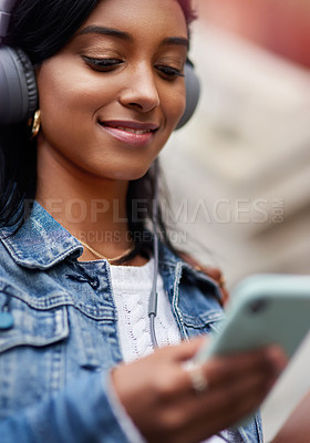 Buy stock photo Shot of a young woman wearing headphones while using her cellphone out in the city