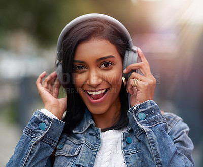 Buy stock photo Cropped shot of a young woman listening to music through her headphones while walking outdoors