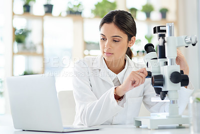 Buy stock photo Shot of a young scientist using a laptop and microscope in a lab