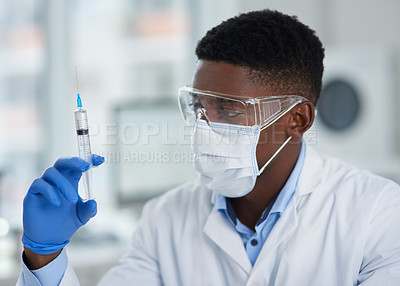 Buy stock photo Cropped shot of an unrecognizable male scientist holding a syringe in his hand while observing it inside of a laboratory during the day