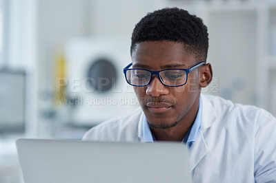 Buy stock photo Cropped shot of a focused young male scientist working on his laptop while being seated inside of a laboratory