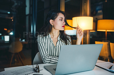 Buy stock photo Shot of a young businesswoman looking bored while working at her desk late at night