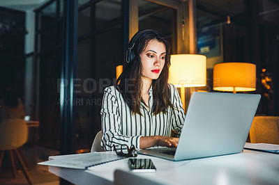 Buy stock photo Shot of a young businesswoman listening to music and using a laptop during a late night at work