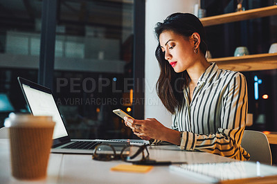 Buy stock photo Shot of a young businesswoman using a smartphone and laptop during a late night at work
