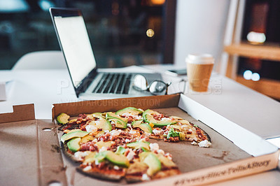 Buy stock photo Shot of a pizza on desk in a modern office late at night