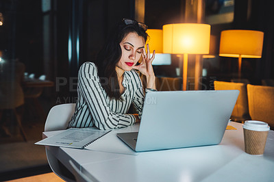 Buy stock photo Shot of a young businesswoman looking stressed out while working at her desk late at night