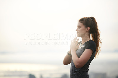Buy stock photo Shot of a sporty young woman meditating outdoors