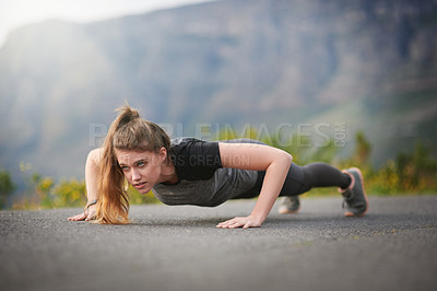Buy stock photo Shot of a sporty young woman doing push ups outdoors
